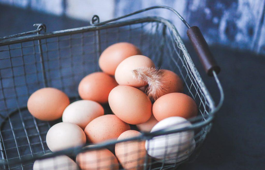 Frische Eier und eine Feder liegen in einem Metallorb