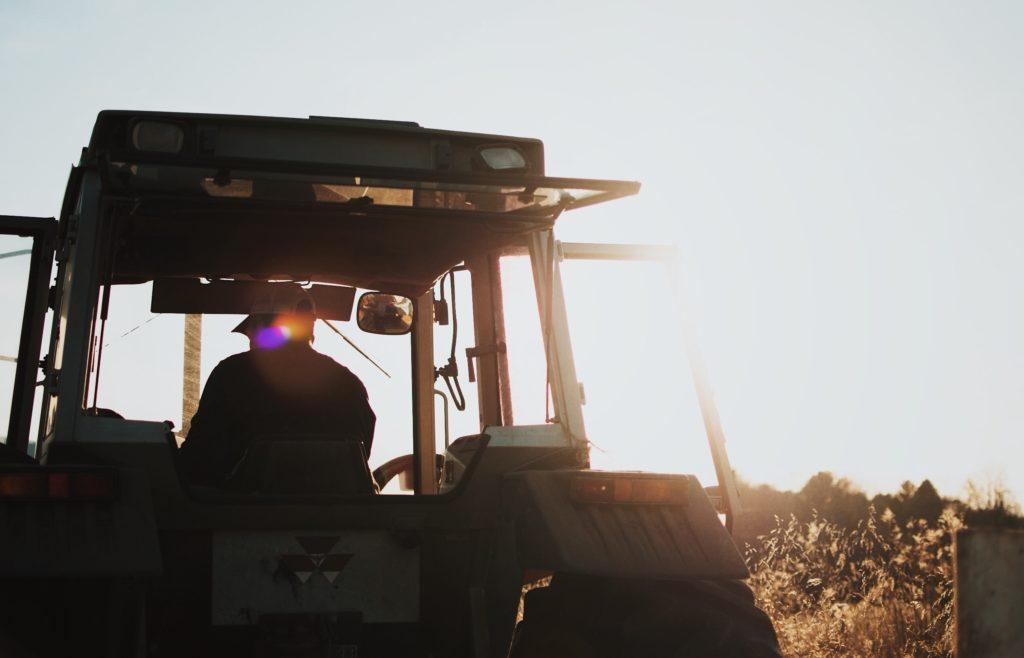 Ein Bauer sitzt auf einem Traktor und fährt über ein Feld